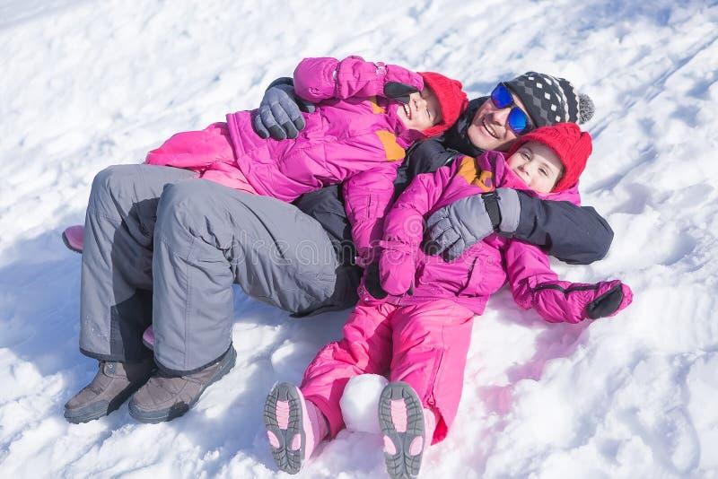 Père et filles ayant l'amusement tout en se trouvant sur la neige photographie stock libre de droits