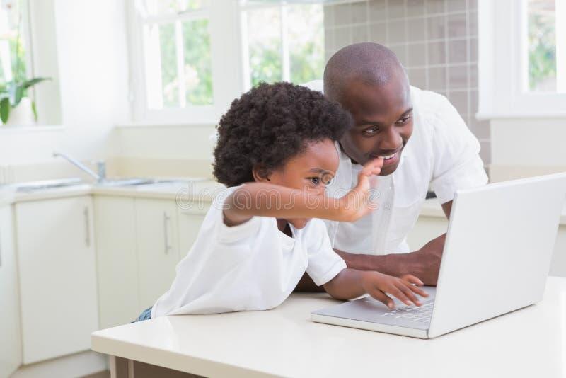 Download Père Et Fils à L'aide De L'ordinateur Portable Sur Le Divan Photo stock - Image du vêtement, garçon: 56484580