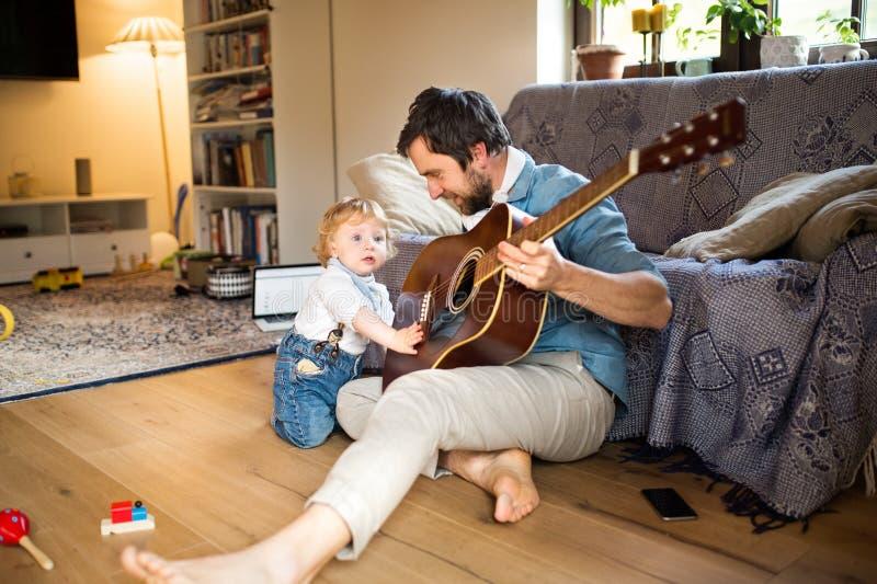 Père et fils à la maison jouant la guitare ensemble photographie stock