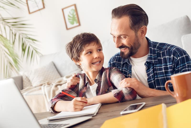 Père et fils à la maison s'asseyant au fils de aide de papa de table faisant la tâche gaie photographie stock