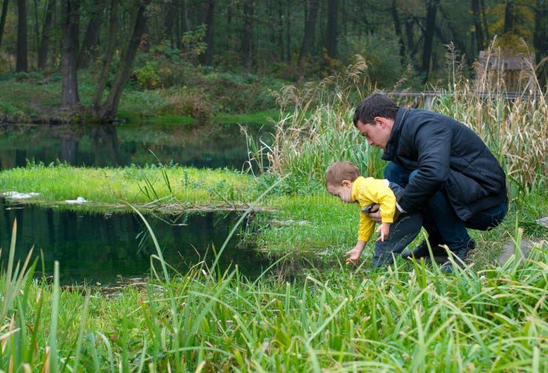 Père et fils au fleuve image stock