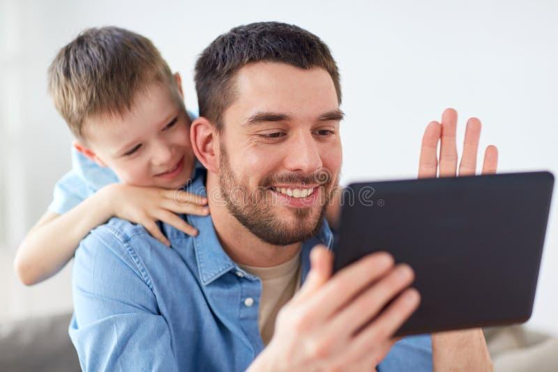 Père et fils avec le PC de comprimé ayant la causerie visuelle image stock