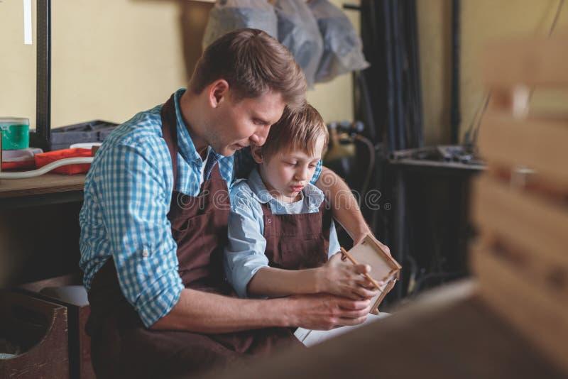 Père et fils avec une maison en bois image stock