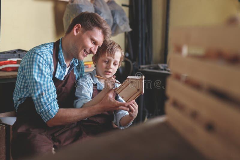 Père et fils avec une maison en bois images libres de droits