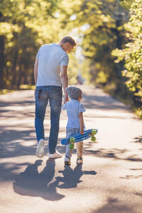 Père et fils avec une planche à roulettes photos libres de droits