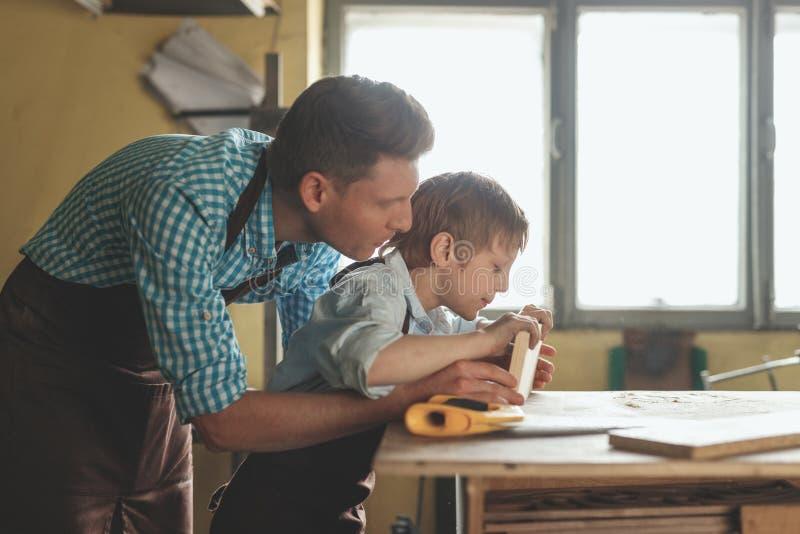 Père et fils avec une planche en bois photo libre de droits