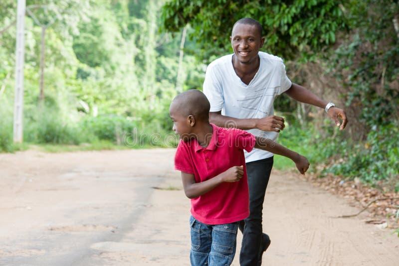 Père et fils ayant l'extérieur courant d'amusement image stock