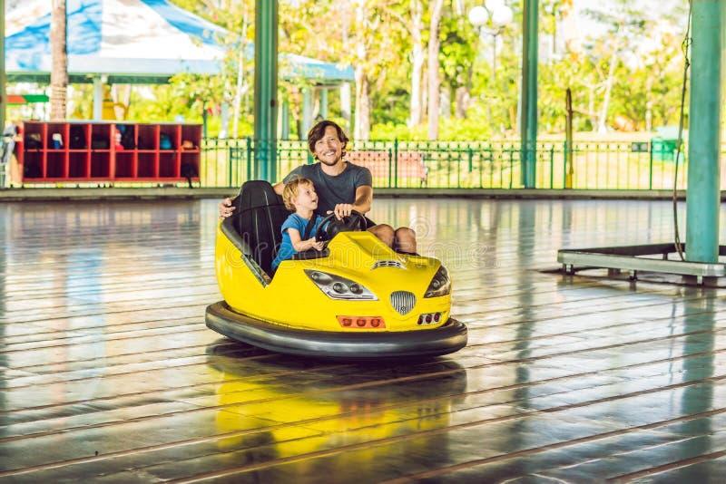 Père et fils ayant un tour dans la voiture de butoir au parc d'attractions photographie stock libre de droits