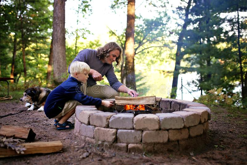 Père et fils commençant le feu de camp en anneau du feu au terrain de camping donnant sur un lac dans les bois image libre de droits