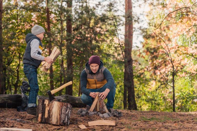 père et fils coupant et rassemblant le bois de chauffage photos stock