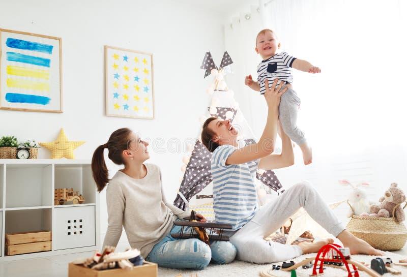 Père et fils de mère de famille jouant ensemble chez le ` s pl des enfants photos stock