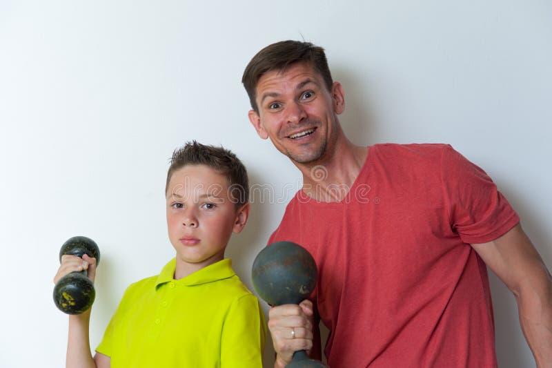 Père et fils de sourire établissant avec des haltères images libres de droits