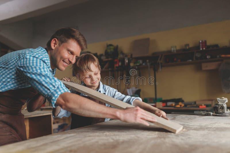Père et fils de sourire en menuiserie photographie stock