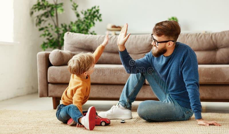 Père et fils donnant cinq hauts à la maison images libres de droits