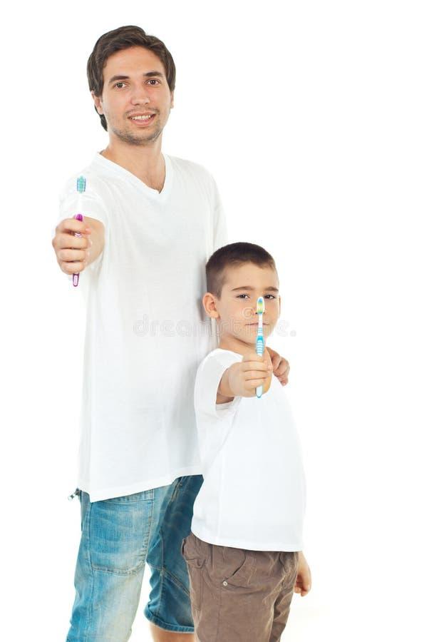 Père et fils donnant des brosses à dents photos stock