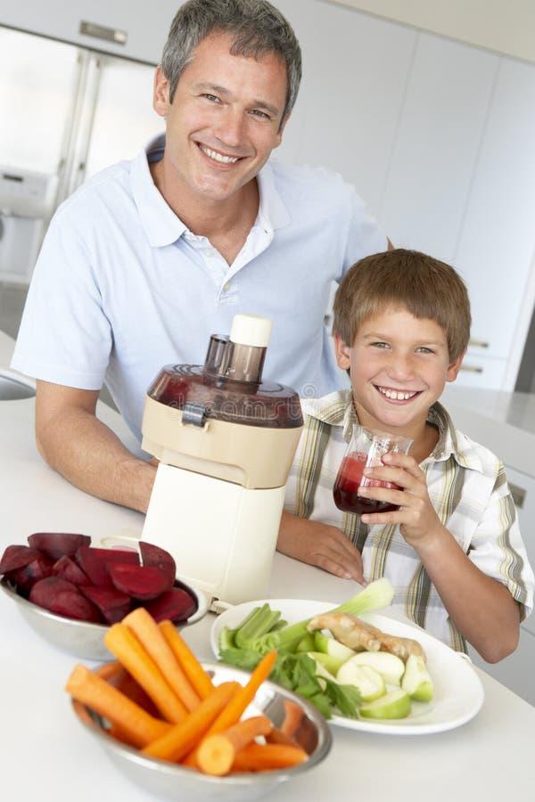 Père et fils effectuant le jus de légume frais photos stock