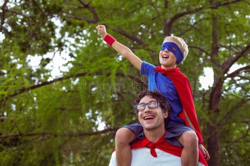Père et fils feignant pour être super héros photo stock