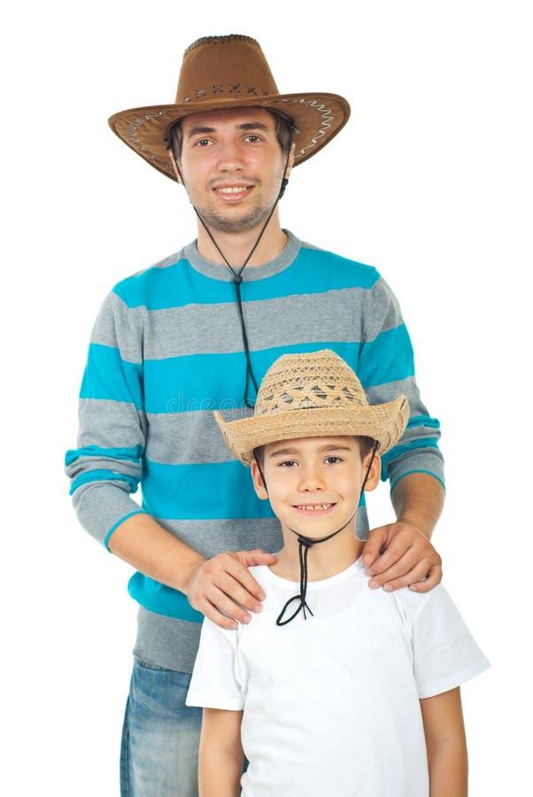 Père et fils heureux avec des chapeaux images stock