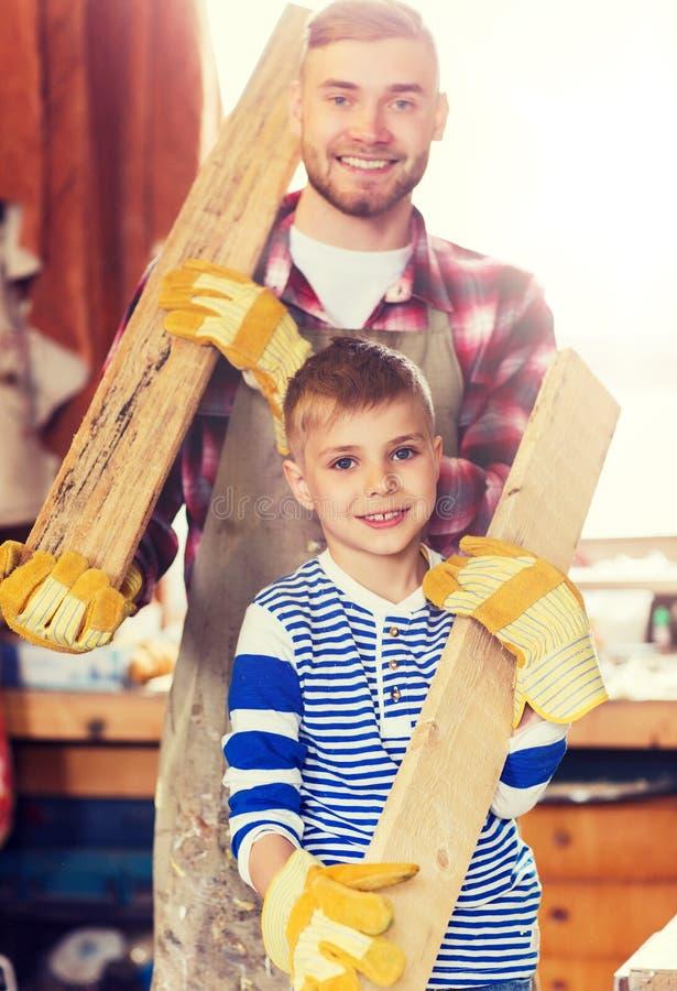 Père et fils heureux avec la planche en bois à l'atelier image libre de droits