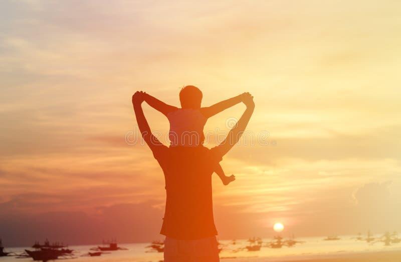 Père et fils heureux sur la plage de coucher du soleil photo stock
