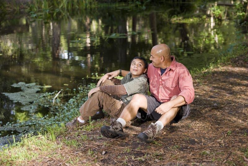 Père et fils hispaniques de verticale à l'extérieur par l'étang photos libres de droits