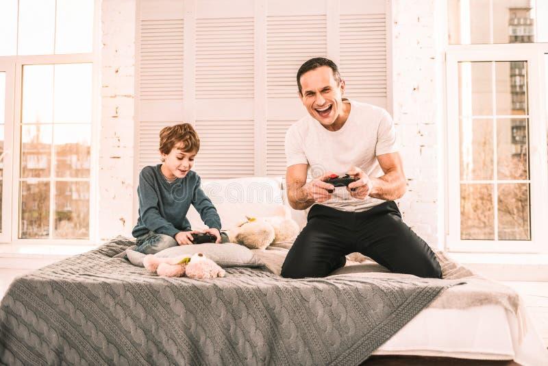 Père et fils immergés en jouant un jeu intéressant photo stock