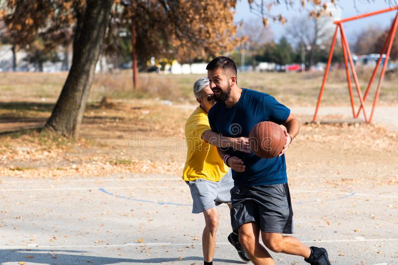 Père et fils jouant au basket-ball en parc photographie stock