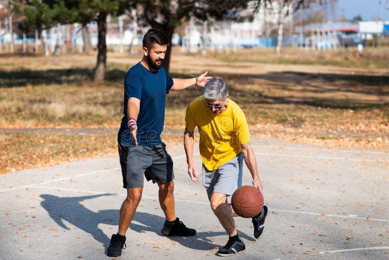 Père et fils jouant au basket-ball en parc photo stock