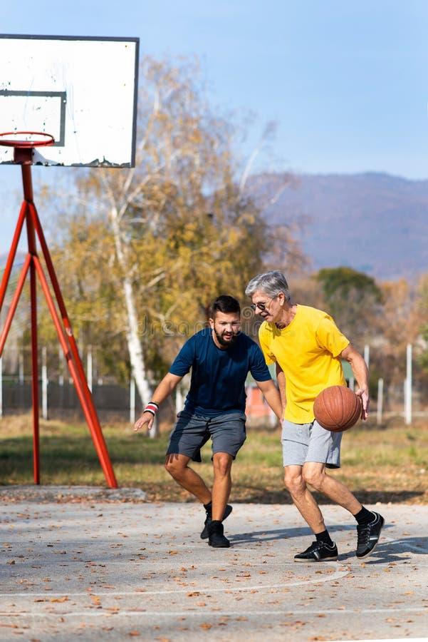 Père et fils jouant au basket-ball en parc photo libre de droits