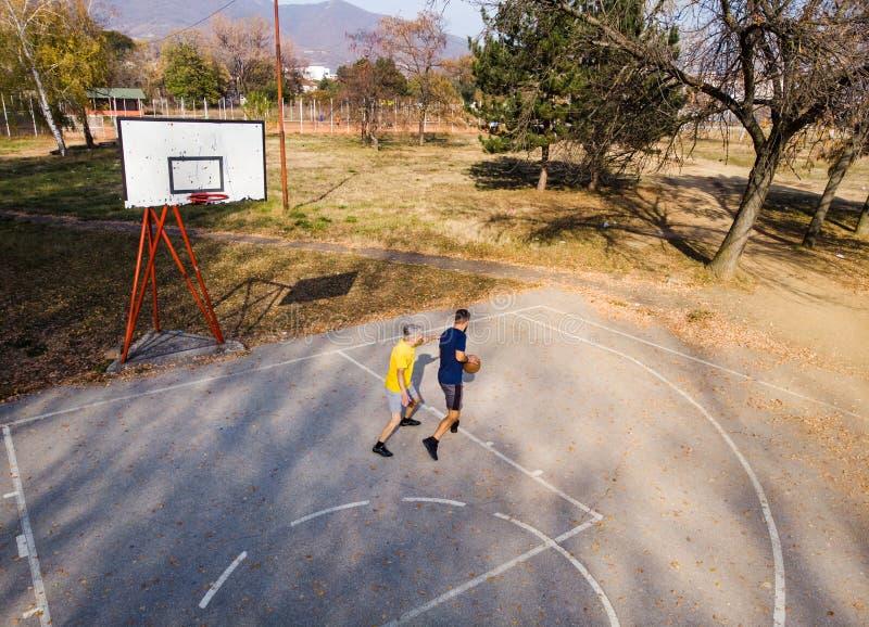 Père et fils jouant au basket-ball en parc images stock