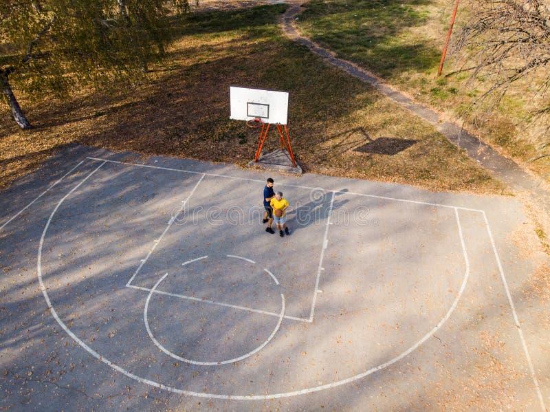 Père et fils jouant au basket-ball en parc image libre de droits