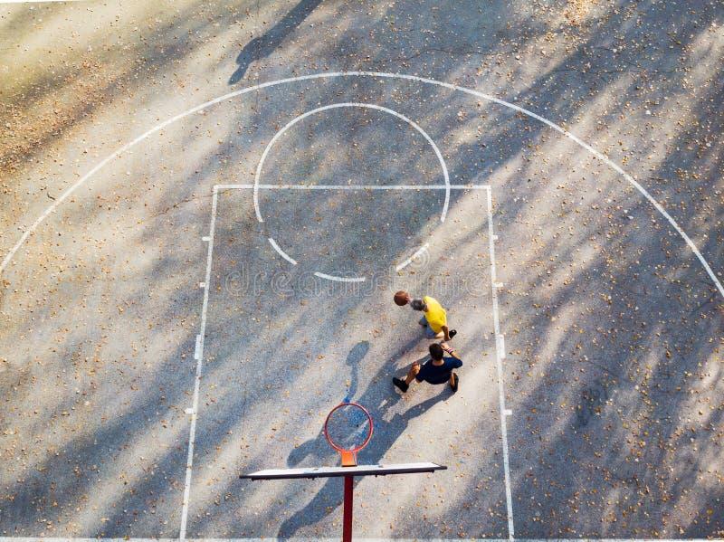 Père et fils jouant au basket-ball en parc image stock