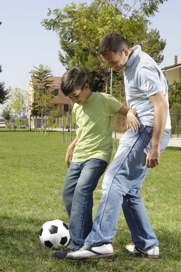 Père et fils jouant au football photos libres de droits