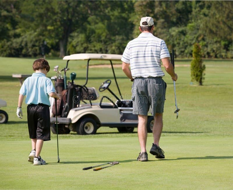 Père et fils jouant au golf photos stock