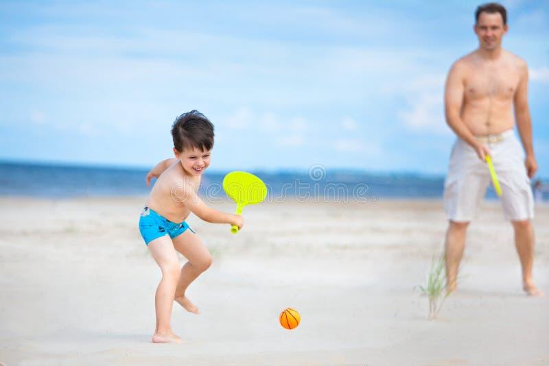 Père et fils jouant au tennis sur la plage images stock