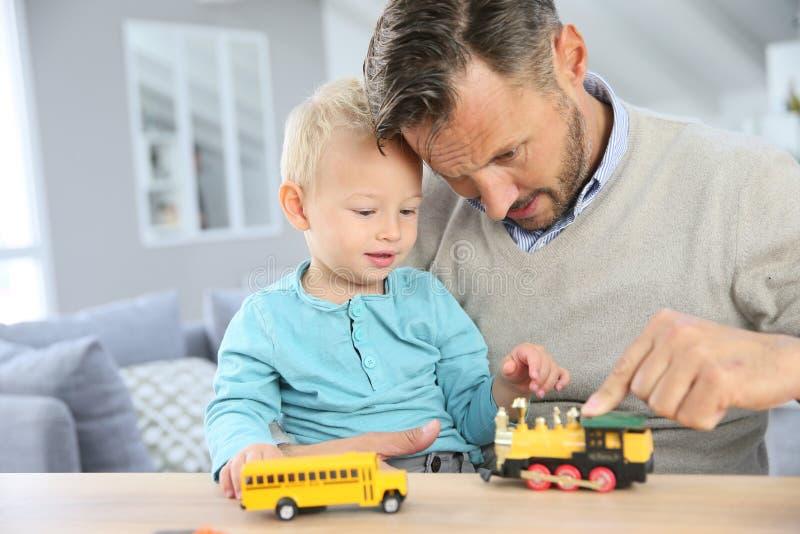 Père et fils jouant avec des jouets de voiture photos stock