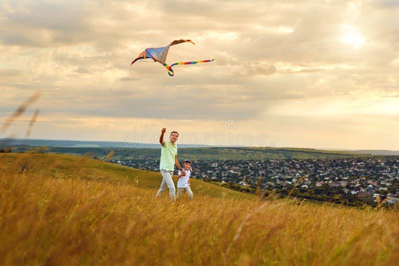 Père et fils jouant avec un cerf-volant en nature image stock