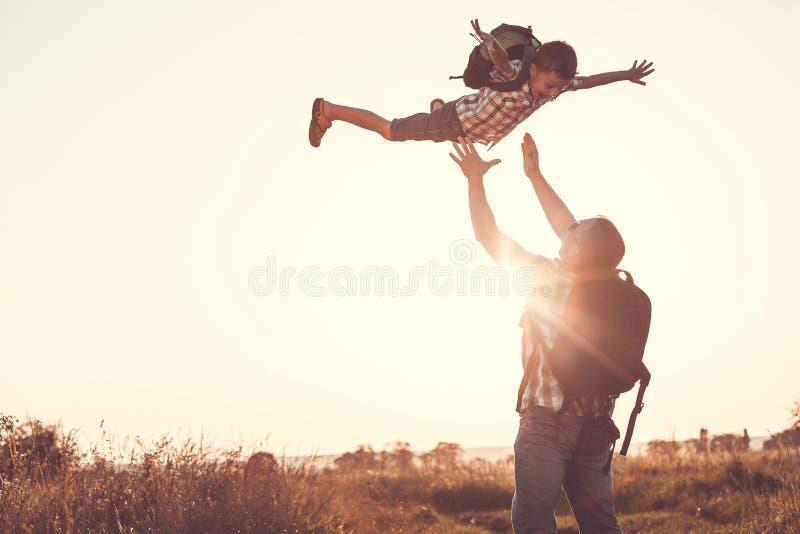 Père et fils jouant en parc au temps de coucher du soleil photos libres de droits