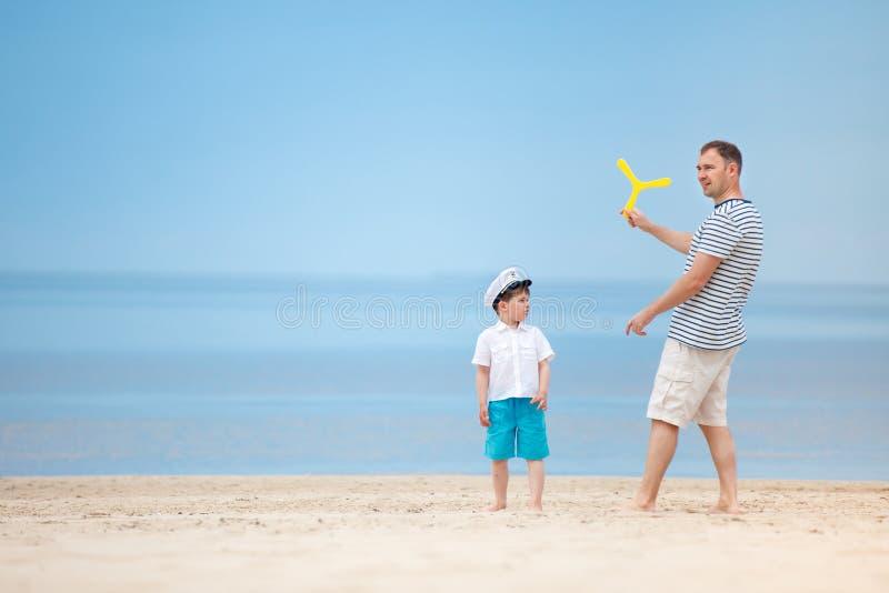 Père et fils jouant ensemble sur la plage image stock