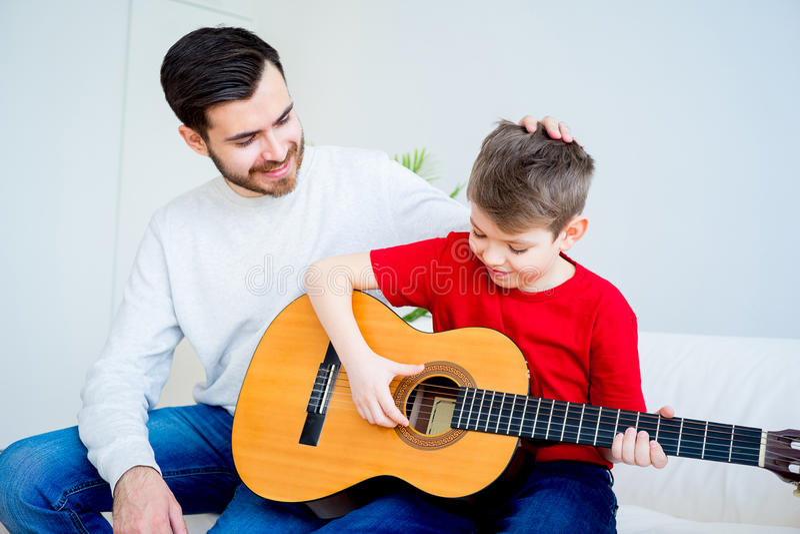 Père et fils jouant la guitare photo stock