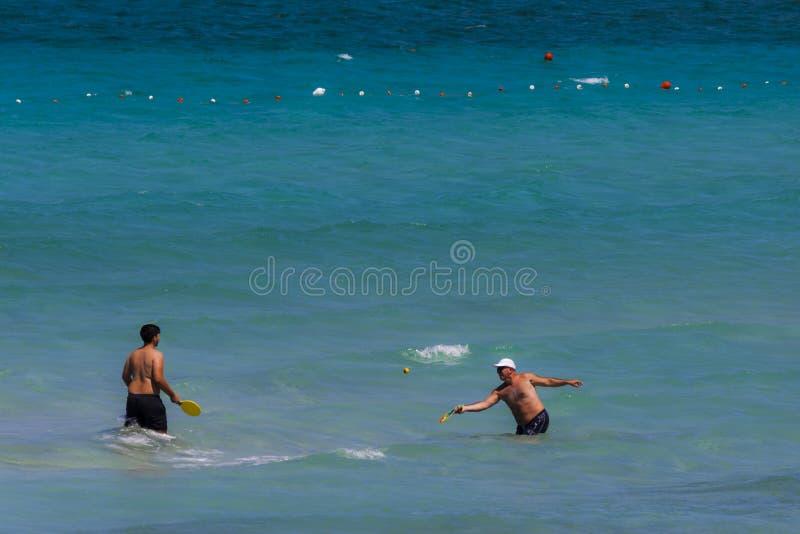 Père et fils jouant le ballon de plage en mer photographie stock libre de droits