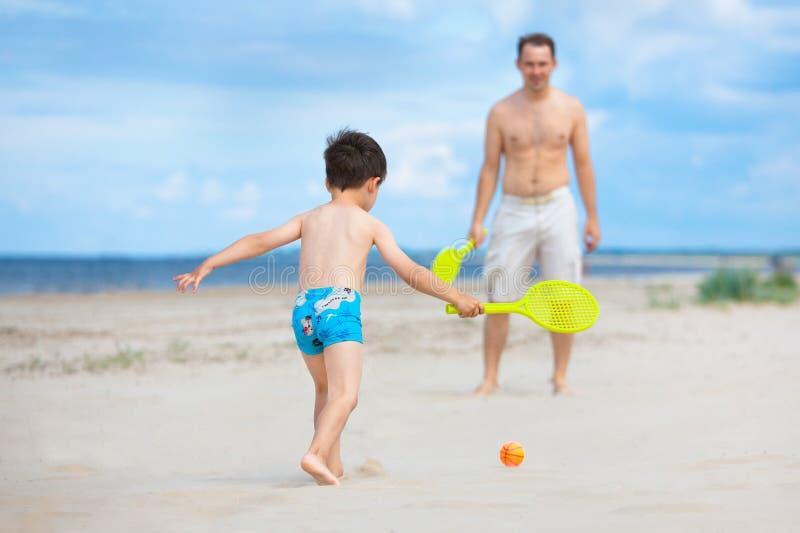 Père et fils jouant le tennis sur la plage photographie stock