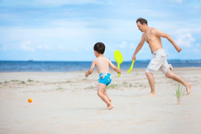 Père et fils jouant sur la plage images libres de droits