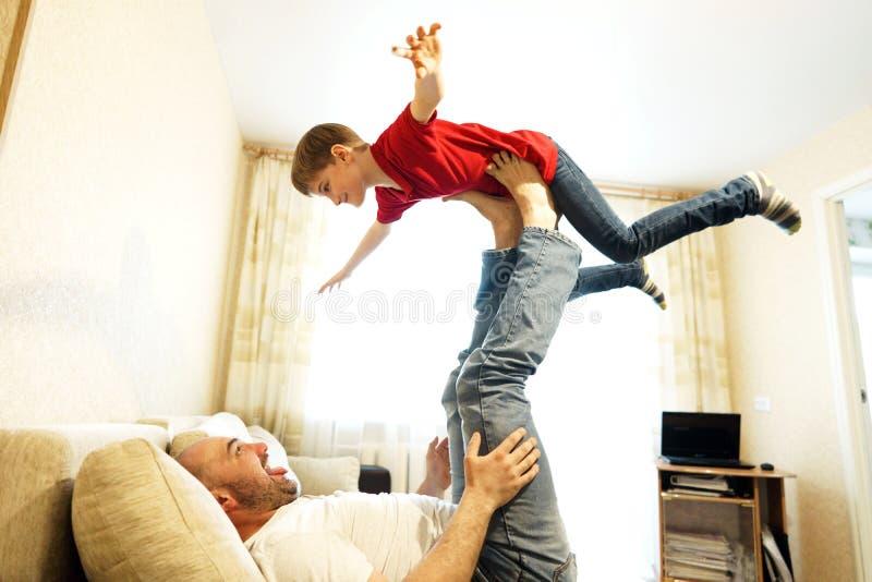 Père et fils jouant sur le divan dans l'avion images libres de droits