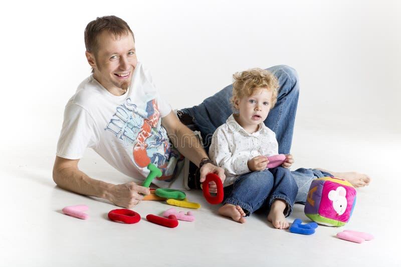 Père et fils jouant sur le plancher d'isolement sur le blanc photo libre de droits