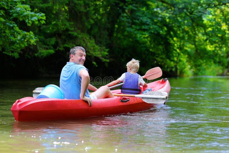 Père et fils kayaking sur la rivière images stock