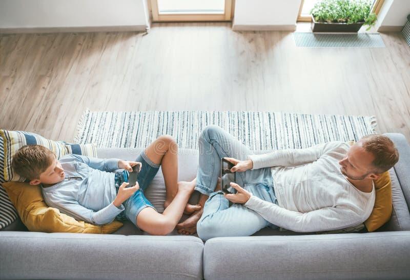 Père et fils Losted dans des appareils électroniques Ils jouant avec le comprimé et le gamepad se reposant dans le salon image libre de droits