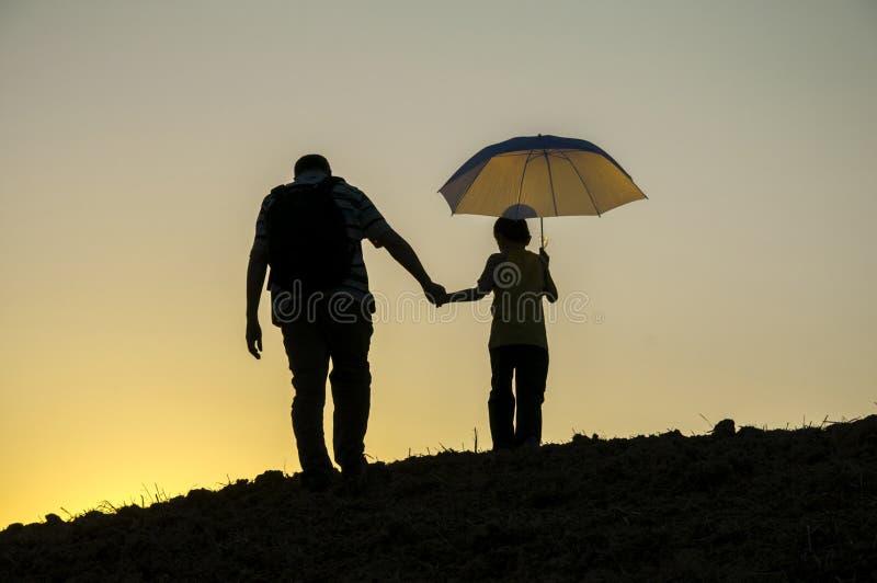 Père et fils marchant dans le coucher du soleil photo libre de droits