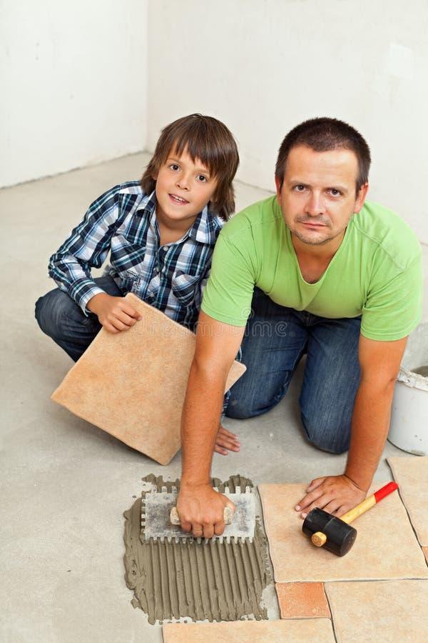 Père et fils montant les carrelages en céramique ensemble images stock
