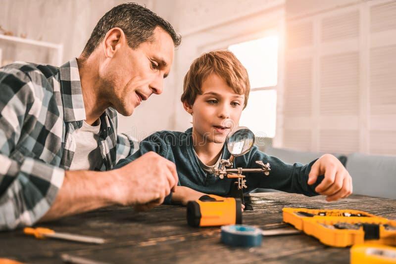 Père et fils observant de petites choses par le psyché image stock